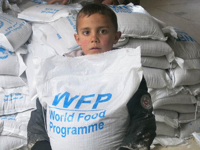 bambino con un sacco di cibo del WFP a un centro di distribuzione