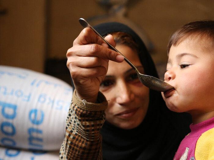 Syrian mother feeding child
